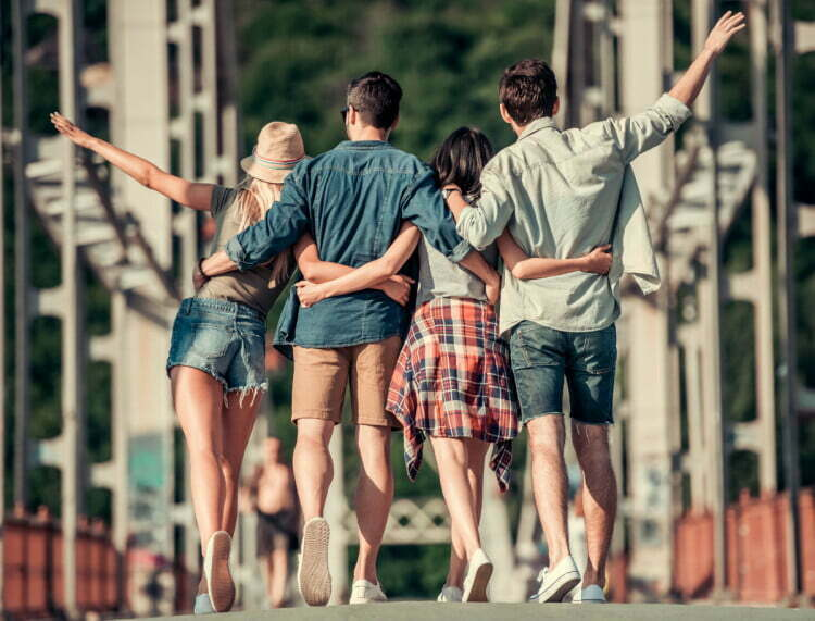 Back view of stylish young people hugging while walking in the city
